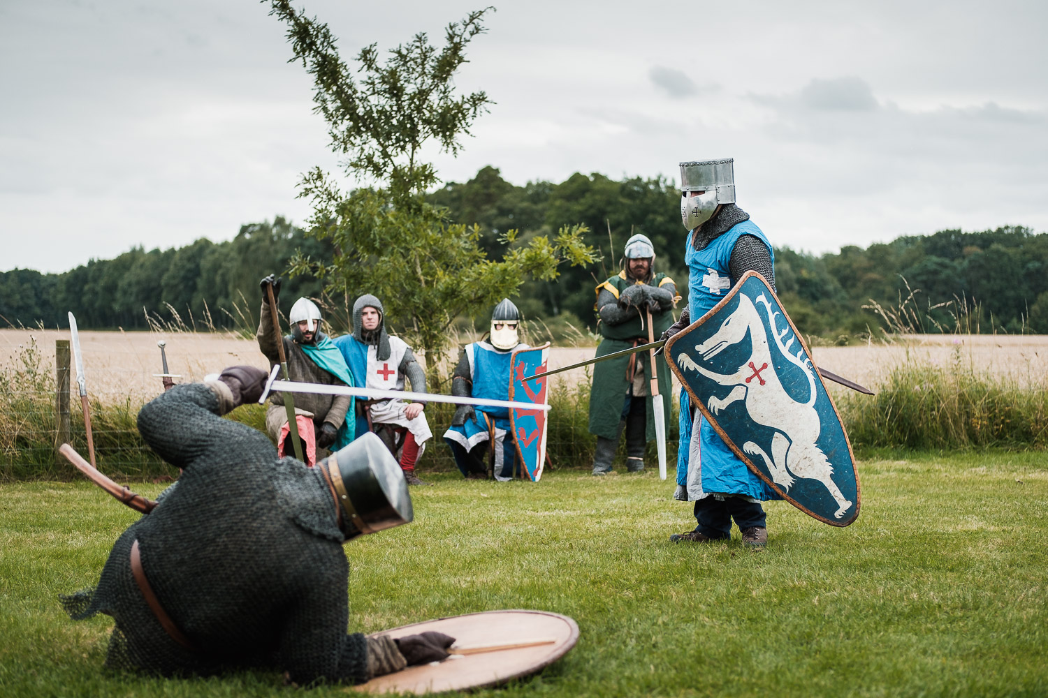 a knight is floored by the groom at the wedding knights tournament