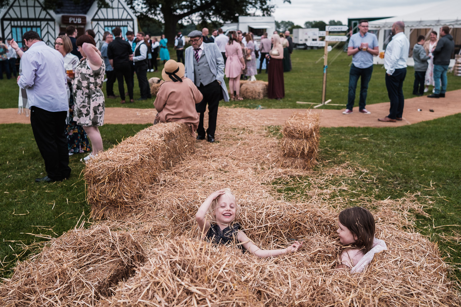 kids play in the hay at an outdoor wedding at the Escrick park estate near York