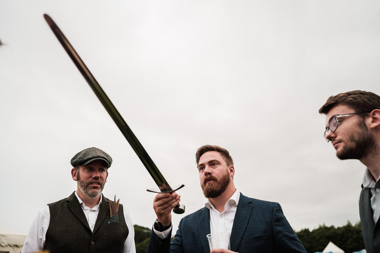 a wedding guest checks out a sword at Escrick park