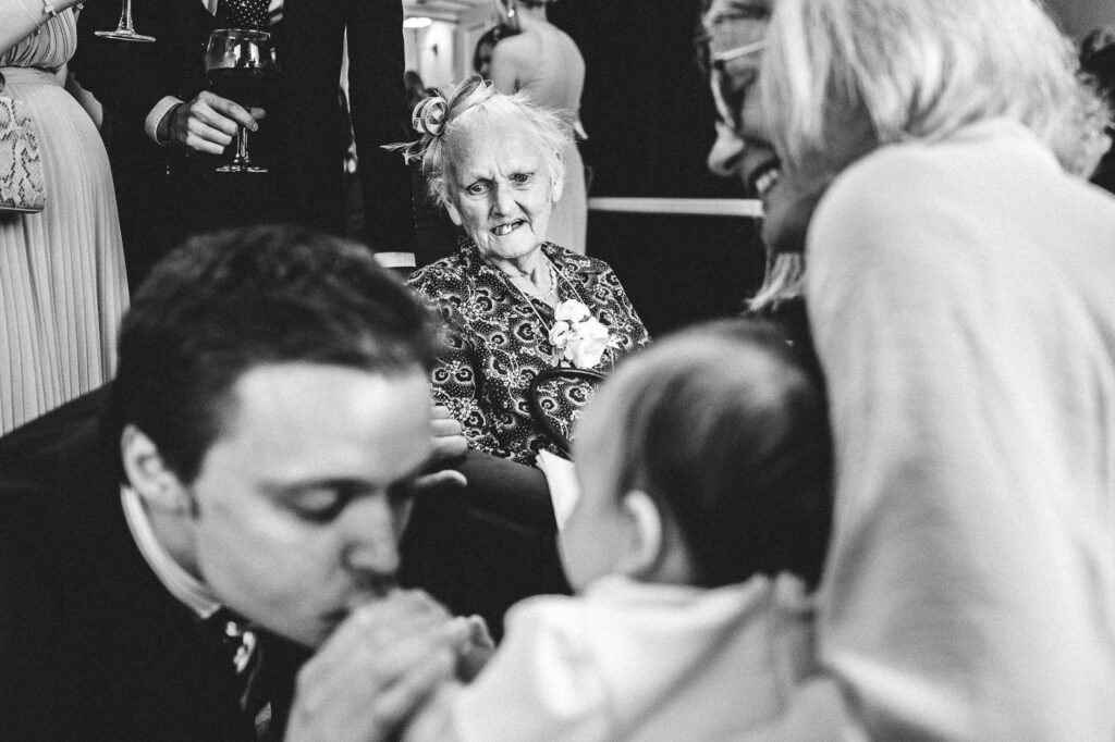great-grandma looks at the baby at the wedding at the old palace in chester