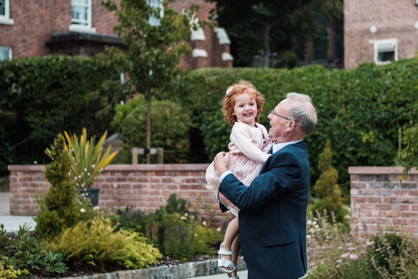 grandad has fun with his granddaughter in the grounds of the old palace in chester at his sons wedding