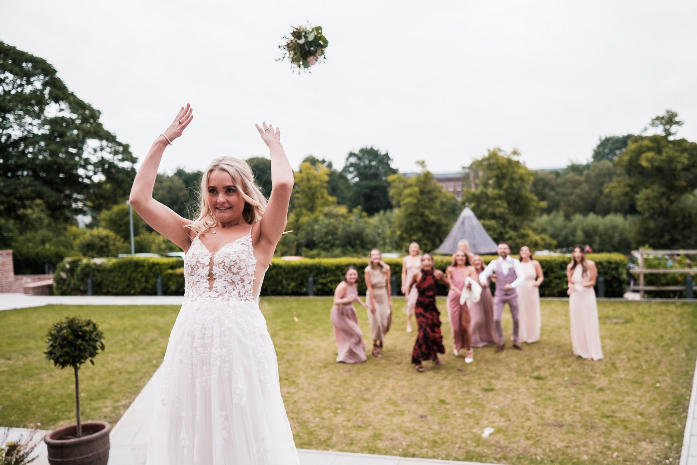 bride throws her bouquet in the grounds of the old palace in chester
