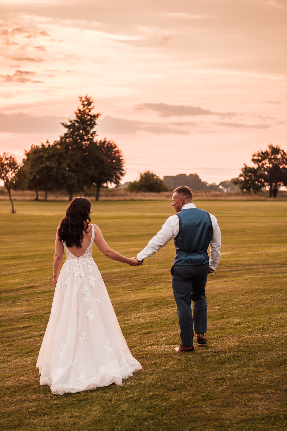 bride and groom walk into the sunset at golden hour at Pryors Hayes golf club