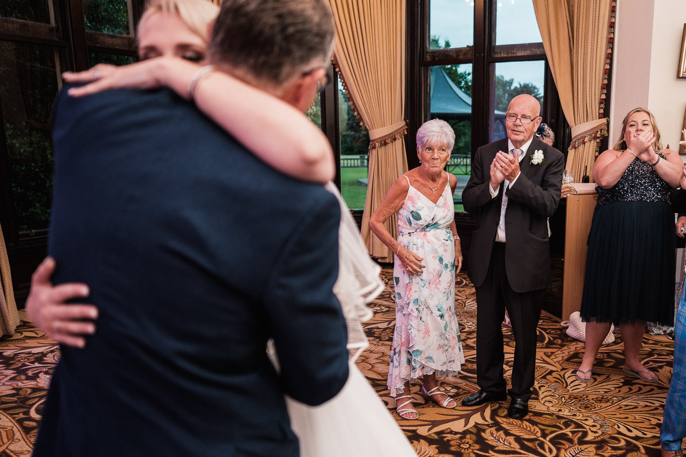grooms parents watch the first dance with dj playing at Walton hall