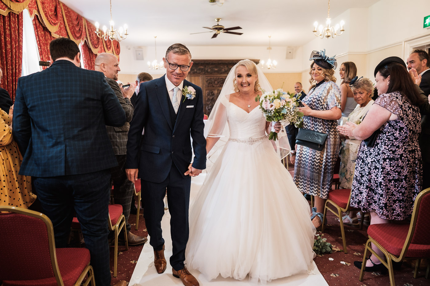 newlyweds walk hand in hand at Walton hall