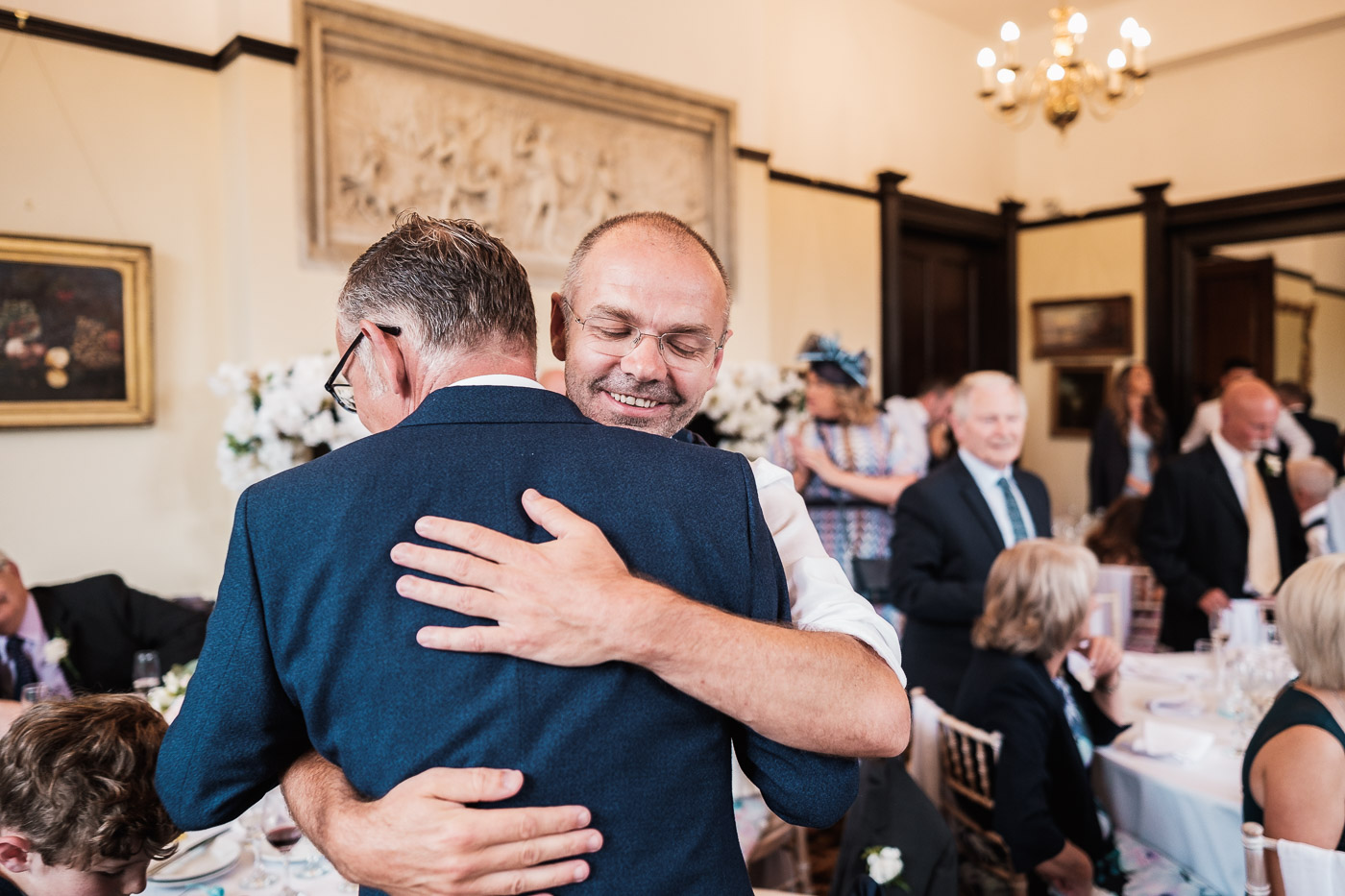Groom embraces best man after speeches at Walton hall in warrington
